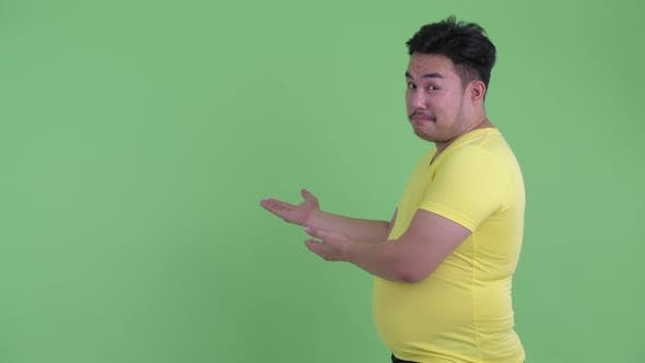 Thumbnail for Happy Young Overweight Asian Man Talking While Showing To Back