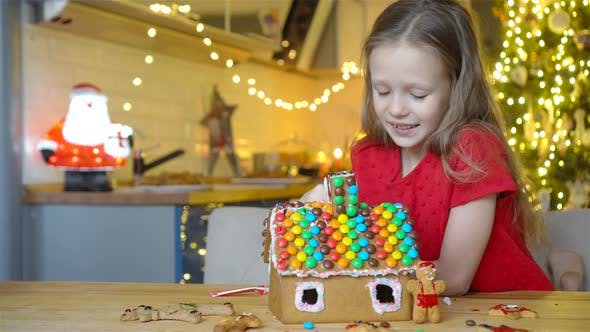 Thumbnail for Little Girls Making Christmas Gingerbread House at Fireplace in Decorated Living Room.
