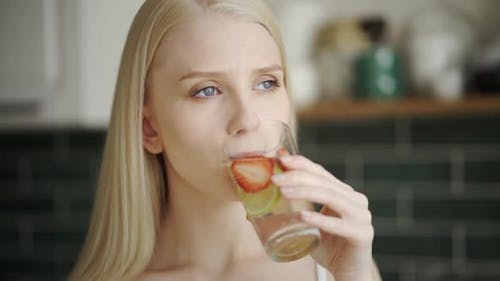 Woman Drinks Refreshing Detox Water with Strawberries and Lime in the Kitchen