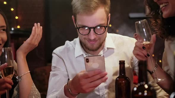 Friends in a Pub Celebrate and Have Fun, One Guy Is Looking at a Smartphone, and Not Talking To