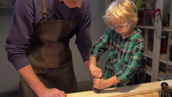 Thumbnail for Boy Fixes the Board on the Table in the Workshop
