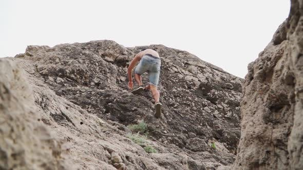 Thumbnail for Athletic Guy Naked To the Torso Climbs Up the Rock. Slow Motion. Lower Angle.