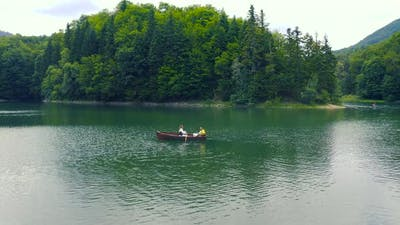 Young Couple are Sailing on a Old Wooden Boat in Lake