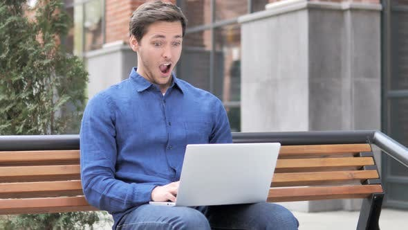 Thumbnail for Sitting Outdoor Young Man in Shock while Working on Laptop
