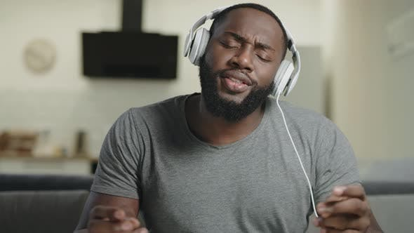 Black Man Singing in Headphones. Portrait of Happy Guy Dancing with Body by stockbusters on Envato Elements