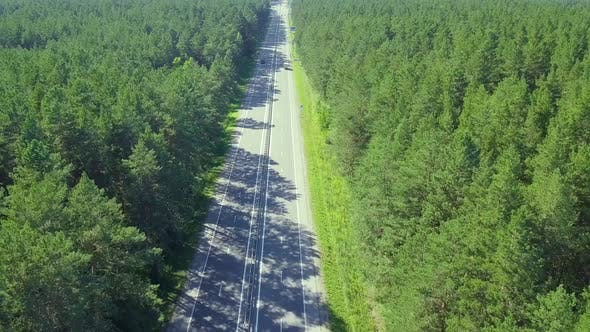 Thumbnail for Aerial: Flying Over Highway, Located in Adense Forest. On the Road Passing Cars and Trucks