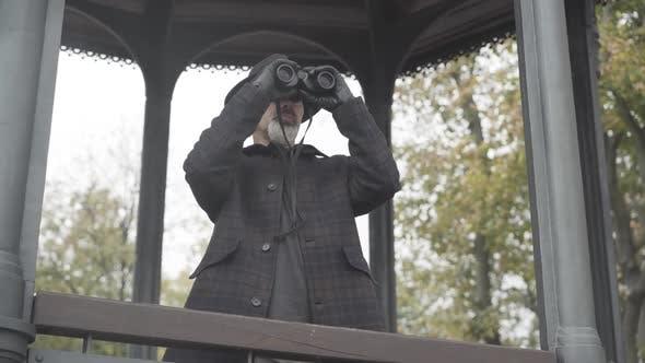 Thumbnail for Mittelaufnahme eines selbstbewussten bärtigen kaukasischen Mannes in Lederhandschuhen, der mit einem Fernglas wegschaut