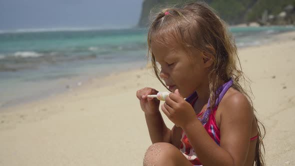 Thumbnail for Little Girl on the Beach with a Lollipop