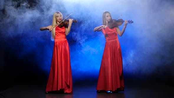 Thumbnail for Two Girls in a Red Dress Playing the Violin. Studio. Smoke