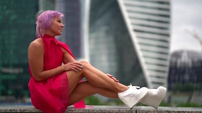 Trendy Dressed Woman in Red Dress and Fashion Boots Is Posing in Urban Landscape