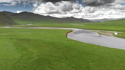 River Flowing Through an Empty Green Meadow with Unmanned and Treeless