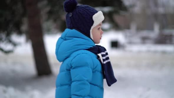 Junge Spaziergänge in verschneite Straße