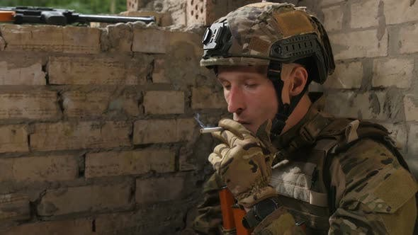 Cover Image for Tired Army Soldier Relieving Stress with Cigarette