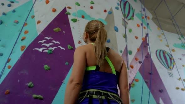 Thumbnail for Fit Young Woman Looking at Climbing Wall at Gym