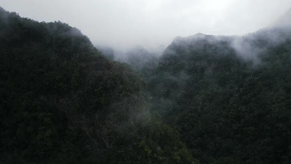 Aerial View Of Mystical Green Mountains Valley Landscape Covered With Clouds Or Fog