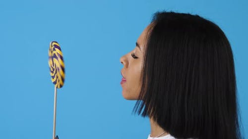 African american woman licking lollipop
