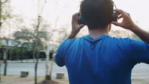 A sporty Asian man wearing headphones ready for running exercise and jogging at the park.