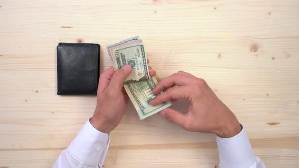 Thumbnail for Hands counting dollar banknotes