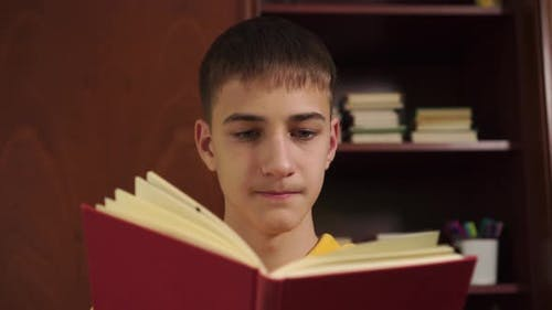 young man in a yellow sweatshirt is reading a book