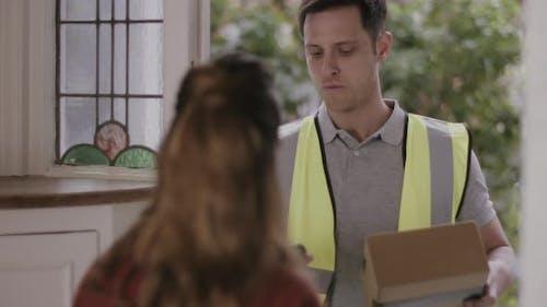 Delivery man delivering parcel at home