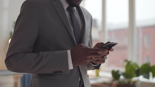 Midsection Shot of Black Businessman Standing in Office and Using Smartphone