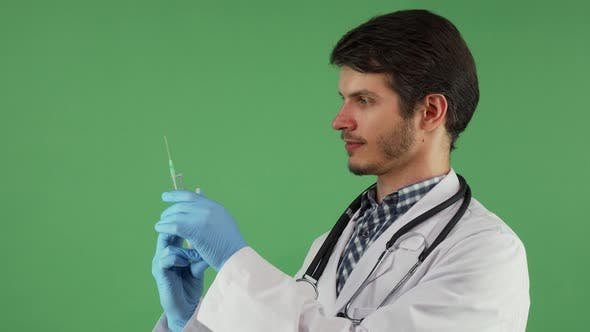Thumbnail for Handsome Male Doctor Preparing Syringe with Vaccine