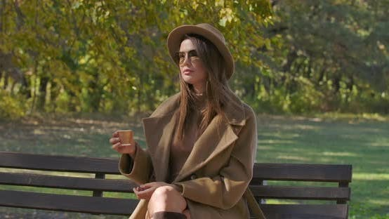Thumbnail for Elegant Caucasian Woman in Brown Hat and Sunglasses Drinking Tea or Coffee As Sitting on the Bench