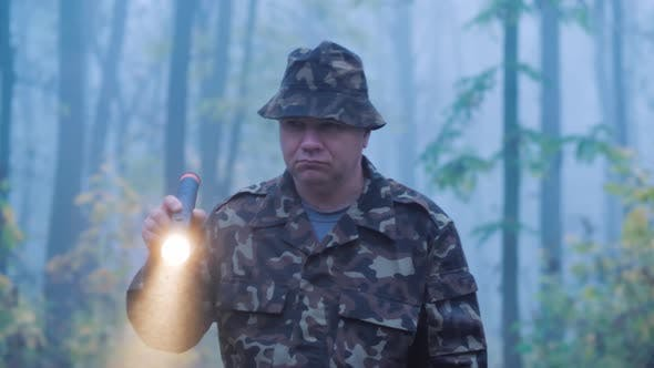 Thumbnail for A Man in Camouflage Is Walking Through the Forest with a Flashlight in His Hand