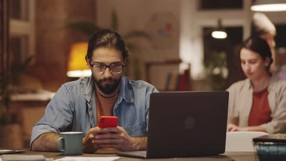 Middle Eastern Man Using Smartphone at Office Desk in Evening