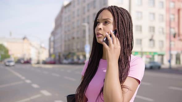 Thumbnail for A Young Black Woman Talks on a Smartphone in the Street in an Urban Area - a Busy Road