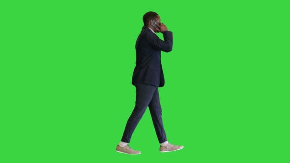 Happy African American Man Walking and Talking on the Phone on a Green Screen Chroma Key