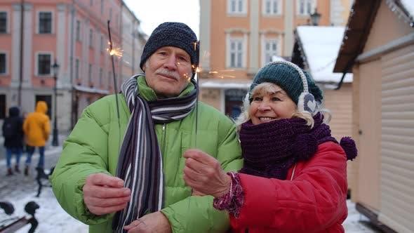 Thumbnail for Senior Happy Couple mit brennenden Wunderkerzen Bengal Lights feiern Geburtstag auf der City Center Street