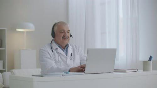 Doctor Is Working with Notebook in His Office in Clinic, Typing Message on Keyboard, Therapist and