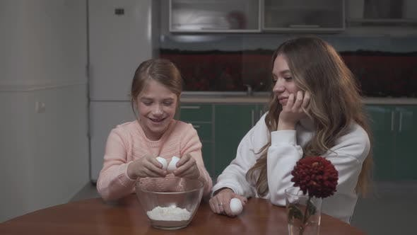 Thumbnail for Girl Breaks a Chicken Egg in Bowl Sitting at the Table in the Kitchen with Her Older Sister