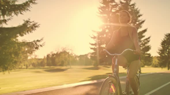 Thumbnail for Fitness Woman Riding Bicycle in Summer Park at Golden Sunset Landscape