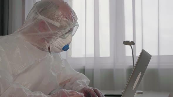 Konzentrierter Virologe trägt Schutzanzug, der mit Laptop arbeitet