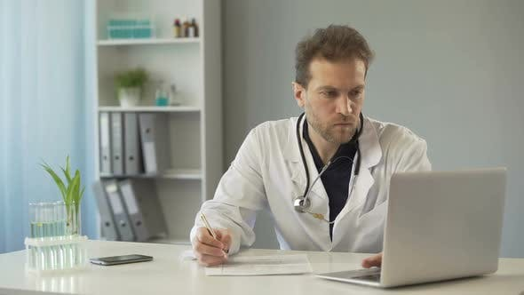Cover Image for Doctor Viewing Test Results on Laptop and Writing Down Medical Records, Medicine