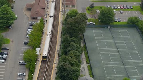 Aerial View of MTA Train Arriving at Station Near Tennis Courts in Long Island