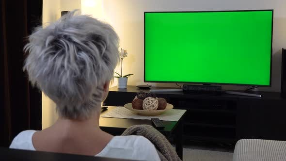 Thumbnail for A Middle-aged Woman Sits on a Sofa in an Apartment Living Room and Watches TV with a Green Screen