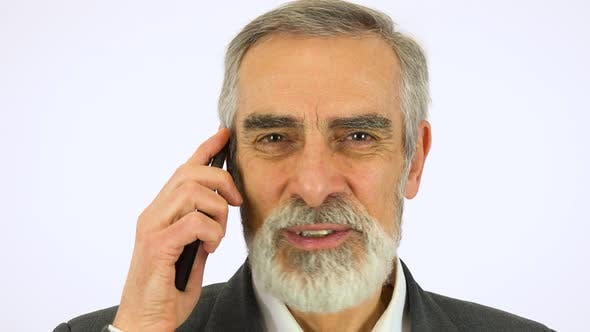 Thumbnail for An Elderly Man Talks on a Smartphone and Looks at the Camera - Face Closeup - White Screen Studio
