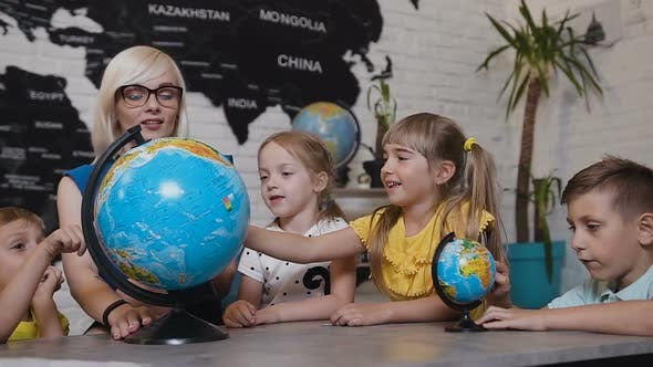 Teacher Looks at Globes in Geography Classroom on the Lesson at the Elementary School