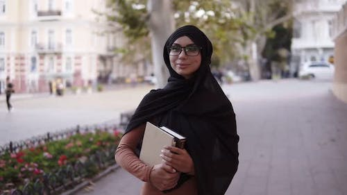 Confident Attractive Muslim Woman in Hijab and Glasses Walking By Streetclose to the College or