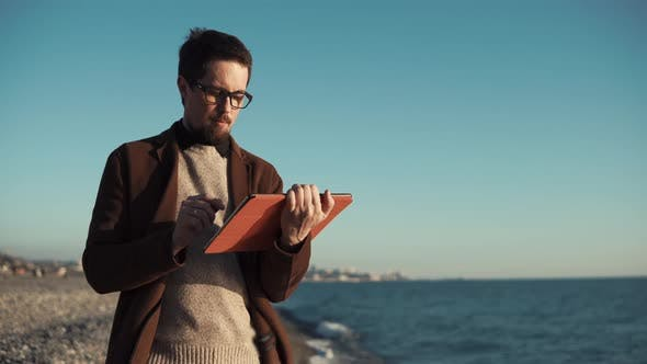 Thumbnail for Bearded Man Is Using Flatbed Computer Sitting on Seashore with Panorama of City