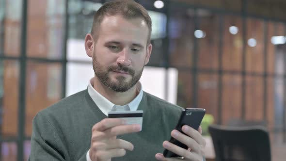 Cover Image for Portrait Shoot of Success Man Added Credit Card in Smartphone