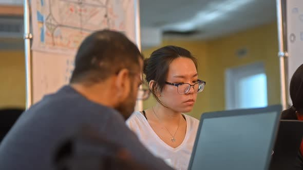 Asian Female Working at an Open Space Coworking Office Looking Focused Using Her Laptop Irrl.