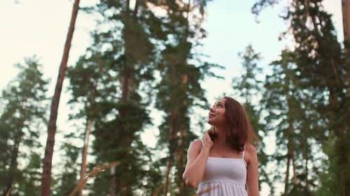 Frau schaut auf einen Baum, bewundert die Kiefern. Im Wald spazieren gehen, die Natur bewundern., 10Bit, ProRes