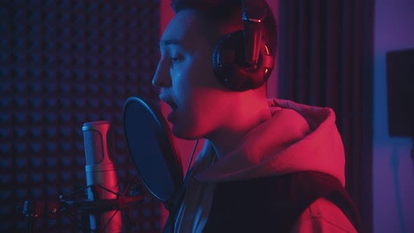 Thumbnail for A Man in Headphones Rapping Through the Pop-filter in the Microphone - Sound Recording Studio