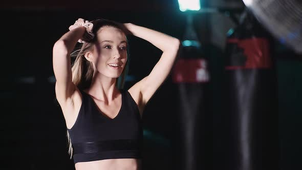 Thumbnail for Attractive Fit Girl with Flowing Hair Smiles at Camera on Fan Background
