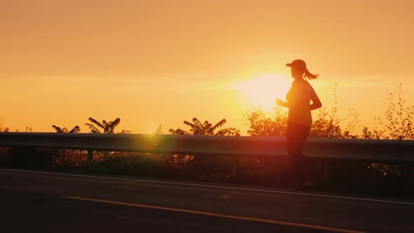 Thumbnail for A Young Woman Runs Along the Road Along the Seashore at Sunset. Silhouette