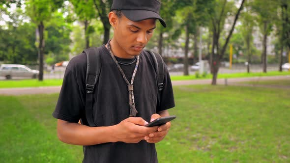 Thumbnail for Portrait Young Man Holding Mobile Chatting Online Outdoors